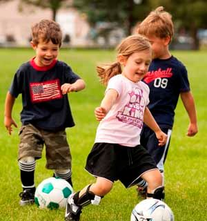 Little Kickers boys and girl kicking soccer balls